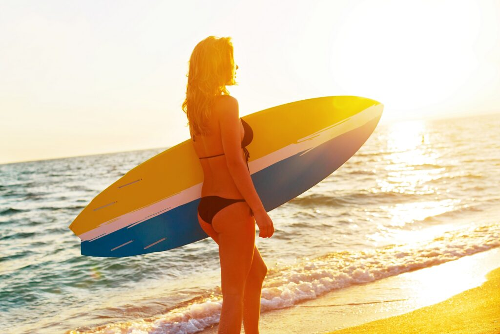 woman with surfboard on mexico beach